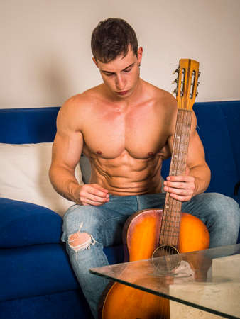 Portrait of muscular shirtless young man playing classic guitar while sitting on couch at home