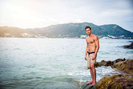 Attractive young man in the sea getting out of water with wet hair, looking in camera. Full length shot