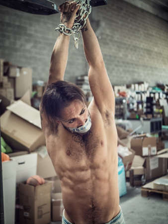 Shirtless adult male with tied hands and duct tape on mouth hanging on chains from ceiling in warehouse Imagens