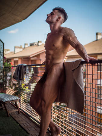 Handsome totally shirtless muscular man outdoor on a balcony or terrace, with towel around his waist