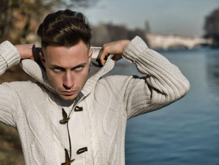 One handsome young man in urban setting in European city, Turin in Italy by the river Po, in cold winter day, looking at camera