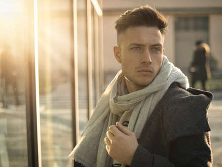 One handsome young man in urban setting in moden city, standing, wearing black coat and scarf in winter day