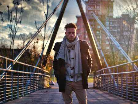 Handsome young man in city setting, with industrial site around him, looking at camera, serious expression