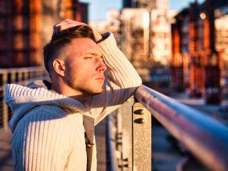 Handsome young man in city setting, with industrial site around him, looking away, serious expression Standard-Bild