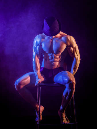 Shirtless muscular bodybuilder performer sitting on stool wearing hat in studio shot with dramatic lighting