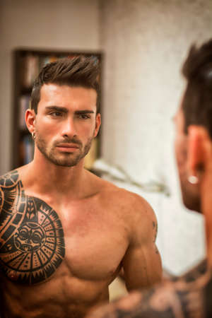 Shirtless muscular handsome man looking at himself in bedroom mirror in the morning Standard-Bild