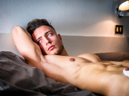 Shirtless sexy male model lying alone on his bed in his bedroom, looking away to a side with a seductive attitude