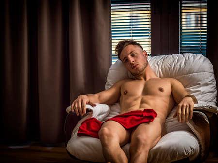 Young seductive man posing naked at home on armchair and looking at camera.