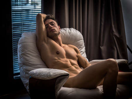 Young seductive man posing naked at home on armchair and looking away. Standard-Bild