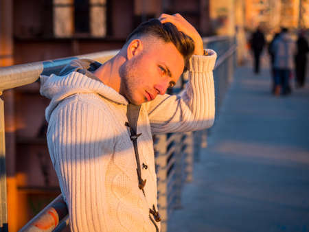 Handsome trendy young man, standing on a sidewalk in city setting at sunset wearing a fashionable sweater or cardigan
