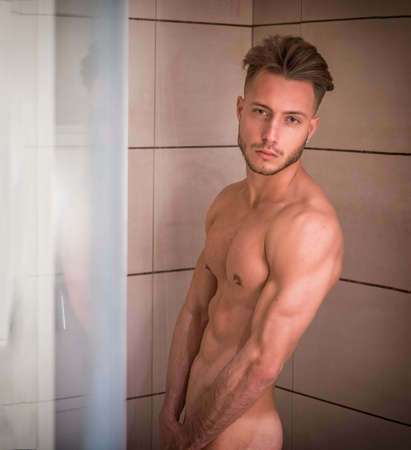 Naked Athletic Young Man Taking Shower in the Bathroom to Refresh While Leaning Against Glass Door, Covering Groin with Hand, Looking at Camera Foto de archivo