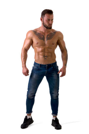 Full body shot of muscular man standing and looking to a side, shirtless