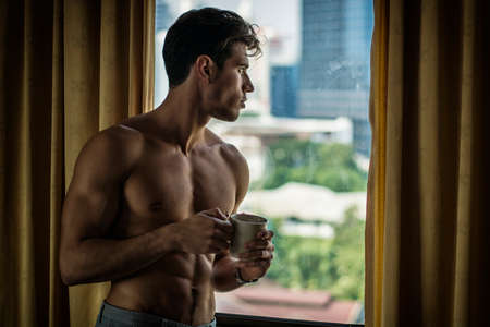Sexy handsome young man standing shirtless in his bedroom drinking a cup of coffee or tea next to window curtains