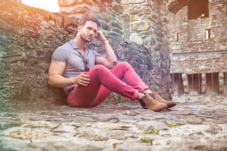 Attractive man outdoor in old European castle, in Switzerland. Athletic build, with tight t-shirt and sunglasses