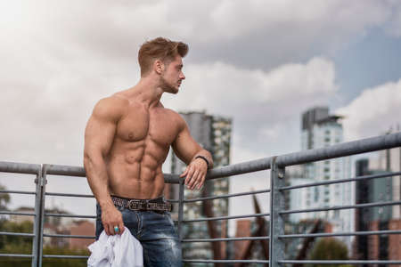 Handsome Muscular Shirtless Hunk Man Outdoor in City Setting. Showing Healthy Body While Looking Away Standard-Bild