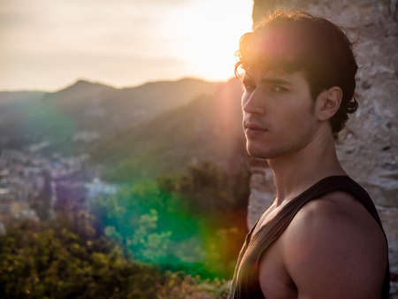 Young Handsome Man Among Trees with Tanktop, Relaxing in Warm Sunlight at Sunset, Looking at Camera