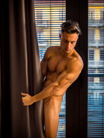 Handsome totally naked muscular young man at home covering nudity with drapes by large windows, in seductive attitude, looking down