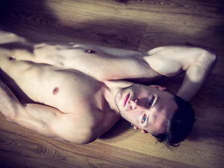 Handsome totally naked muscular young man laying down on hardwood floor at home in seductive attitude, looking at camera Standard-Bild