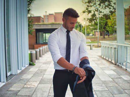 Handsome young business removing business suit jacket, outdoor in city setting Standard-Bild