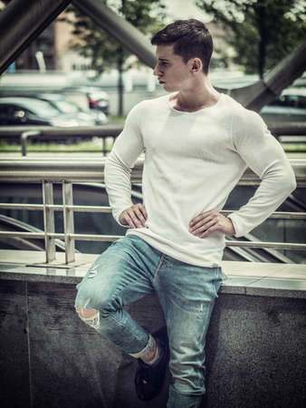 Muscular young man wearing white shirt and jeans in city setting Standard-Bild