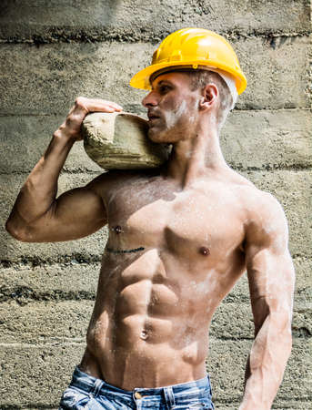 Handsome muscular construction worker standing shirtless in front of a concrete wall, looking away to a side Standard-Bild