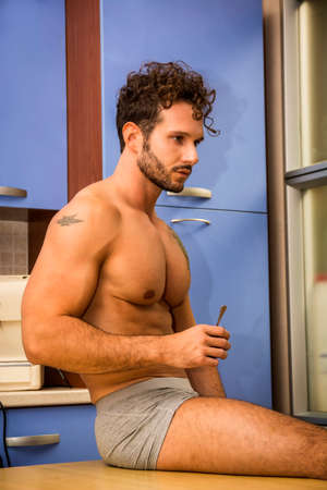Sexy young man in underwear sitting with cup of coffee on kitchen table Standard-Bild