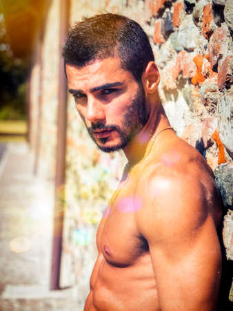 Shirtless handsome athletic young man outdoor standing against old brick wall looking at camera Standard-Bild