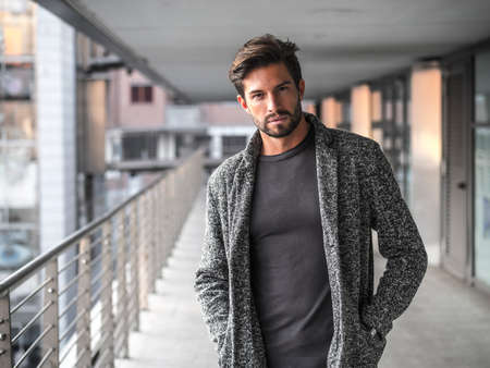 One attractive man in urban environment in city, walking, wearing cardigan