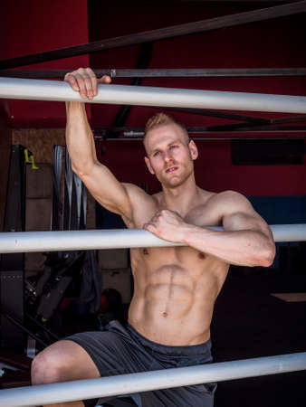Handsome muscular young man standing against horizontal bars, looking at camera