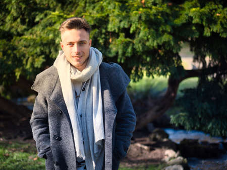 Handsome young man outdoor in winter fashion, wearing black coat and woolen scarf in city park Standard-Bild