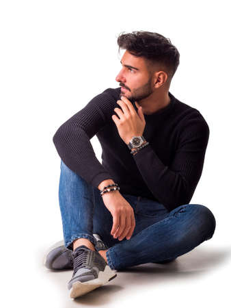 Full body shot of handsome young man with shirt and jeans sitting on the floor, isolated on white Standard-Bild