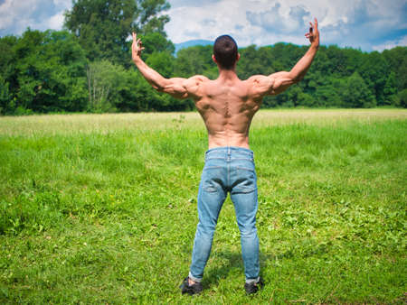Back of Muscular Shirtless Young Hunk Man Outdoor in Nature Standing on Grass. Showing Healthy Muscle Body While Looking away Standard-Bild