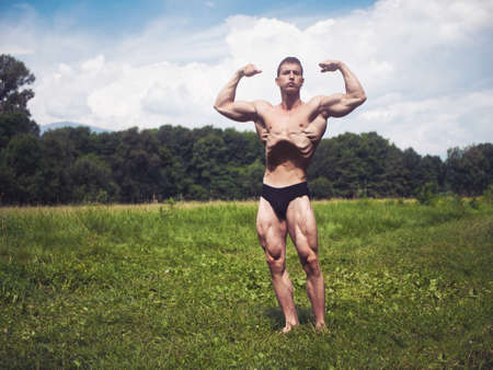 Handsome Muscular Shirtless Young Hunk Man Outdoor in Nature Standing on Grass. Showing Healthy Muscle Body While Looking away
