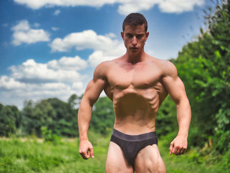 Handsome Muscular Shirtless Young Hunk Man Outdoor in Nature Standing on Grass. Showing Healthy Muscle Body While Looking at Camera