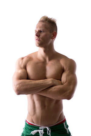 Shirtless muscular young man standing with arms crossed on chest, looking away to a side, isolated on white