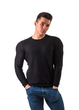 Cool young man with wool sweater on white background looking at camera, with hands in pockets of jeans pants