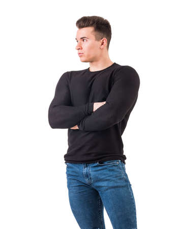 Handsome young man in black sweater standing, looking to a side, arms crossed on chest, isolated on white