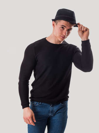 Young man tipping his hat, touching fedora hat on his head, in studio shot on white background
