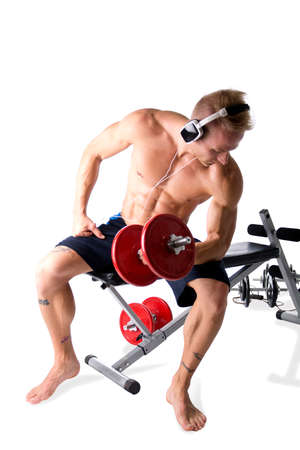Portrait of a muscular blond young man lifting weights and listening to music in headphones, isolated over a white background Standard-Bild