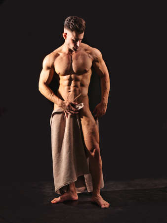 Handsome totally naked muscular bodybuilder young man covering with towel, isolated on black background