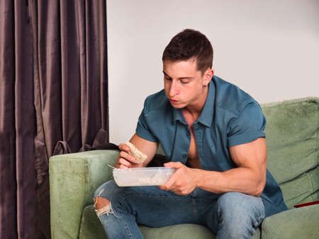 Hungry muscular young man gulping down food, looking at it as he takes another mouthful Standard-Bild