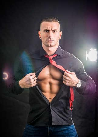 Muscleman opening his shirt revealing muscular torso, on dark background