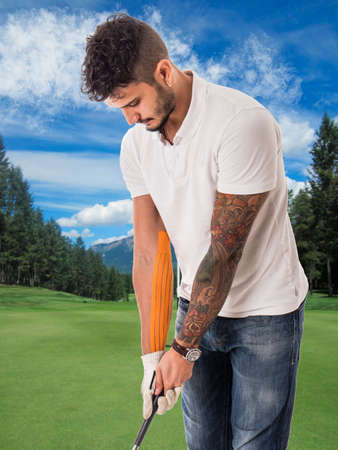 Man playing golf in green field with adhesive tape on arm