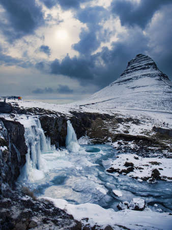 Frozen famous waterfall near mountain in Iceland