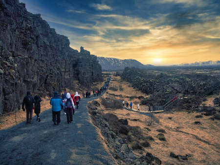 Tourists or hikers walking along country road in Iceland