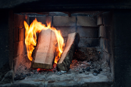 stone fireplace: Fireplace. Logs firewood burning at a stone fireplace outdoors.