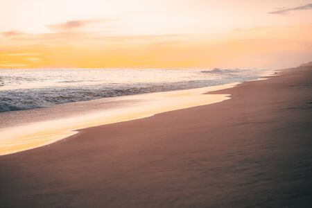 Pacific waves and sandy beach at sunset in Mexico
