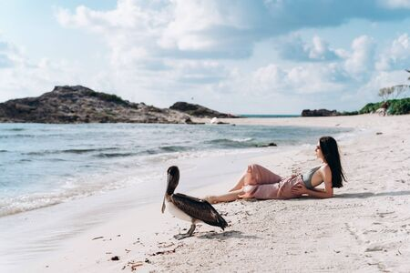 A girl in pink pants sits on the Caribbean Sea near to a pelican in Mexico