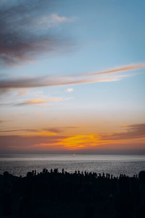 A crowd of people admire the sunset on a cliff on the Pacific Ocean in Mexico