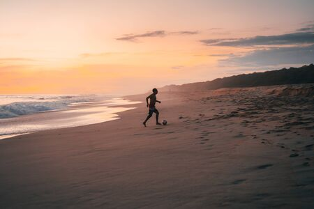 Silhouette of a man with a ball running on the sandy beach of the Pacific Ocean in Mexico